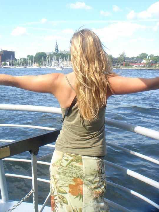 Jeune fille de dos sur un bateau prenant la mer